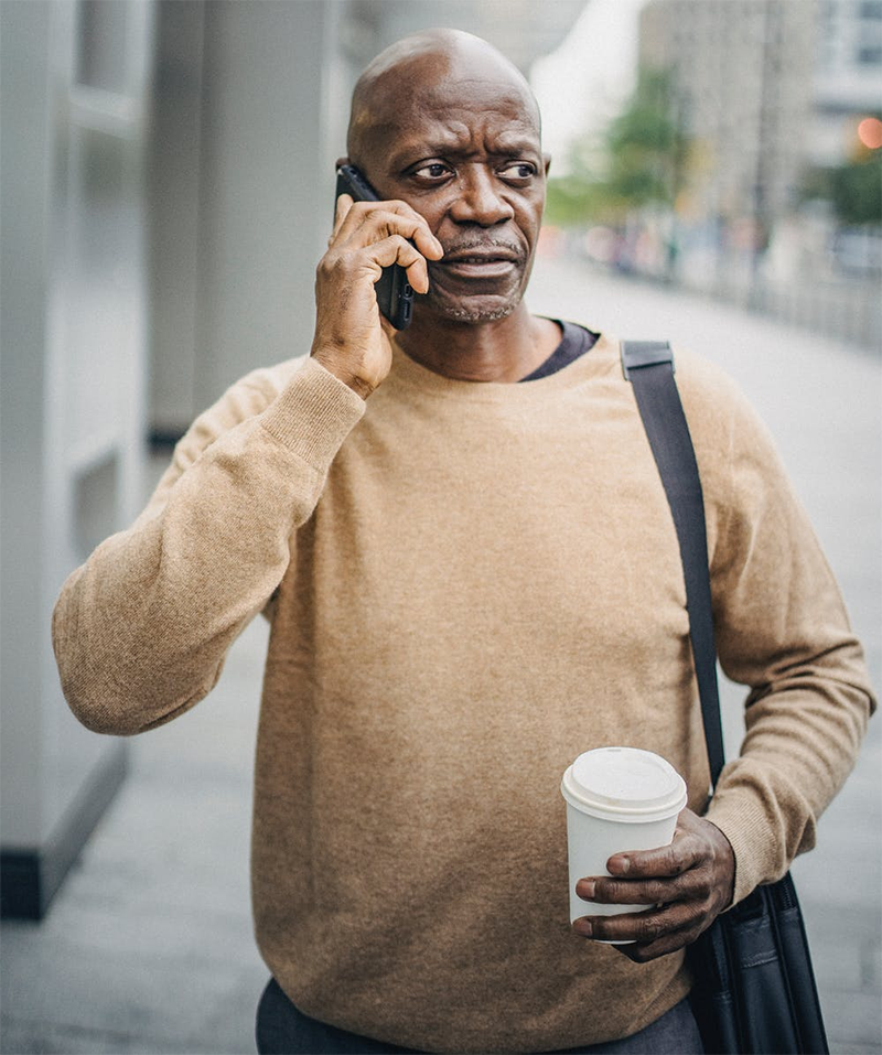 man in tan sweater talking on cell phone on city street